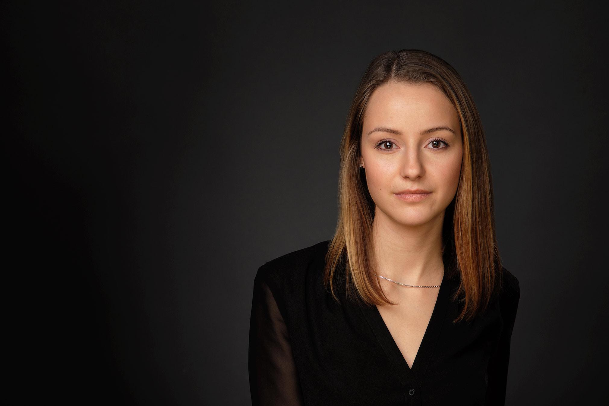 Das Bild zeigt ein Bewerbungsfoto einer brünetten jungen Frau in schwarzem Top mit V Ausschnitt vor dunklem Hintergrund