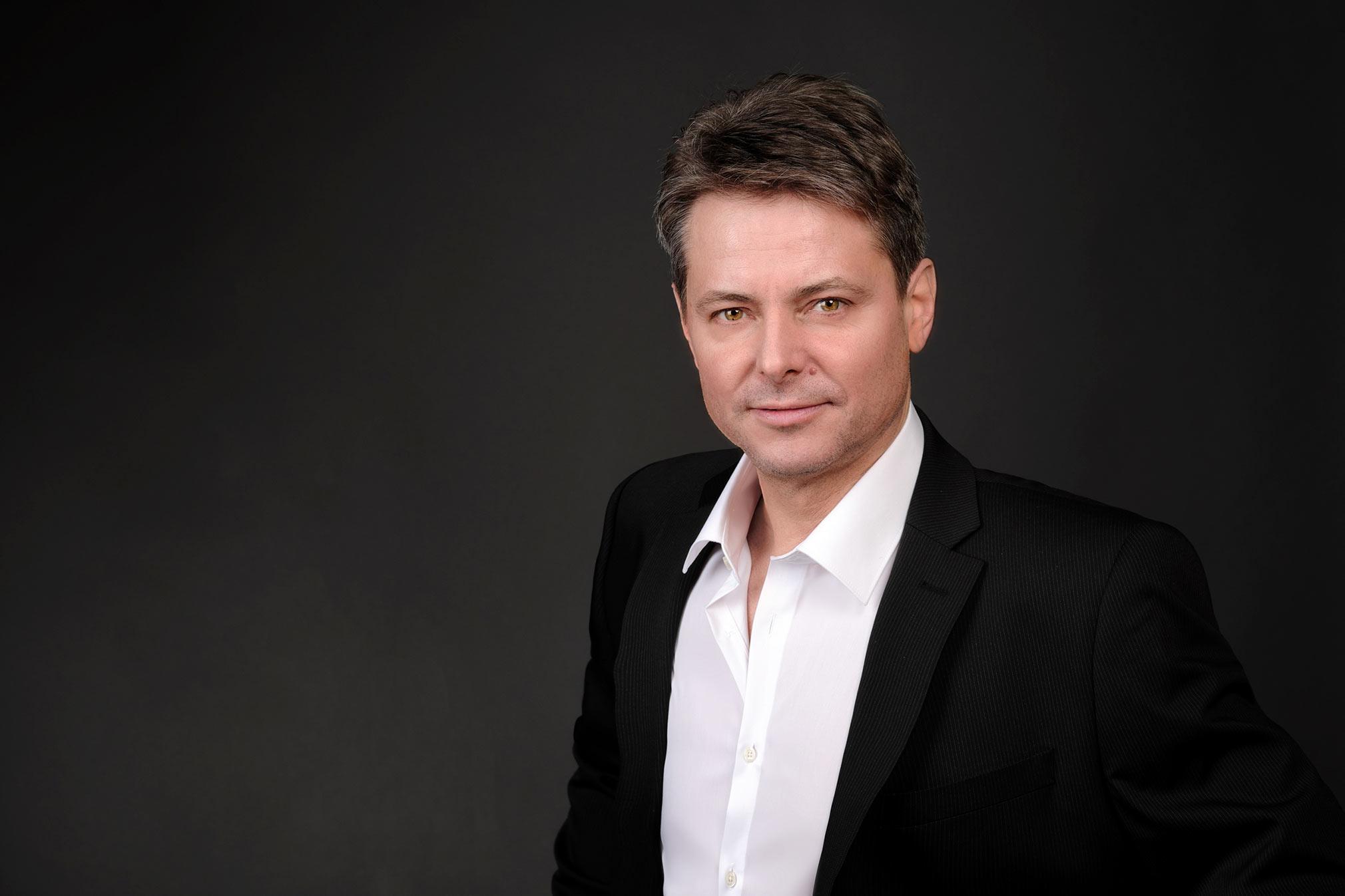 Das Bild zeigt ein Businessfoto eines Mannes im Halbprofil gekleidet mit einem weißem Hemd und schwarzem Sakko