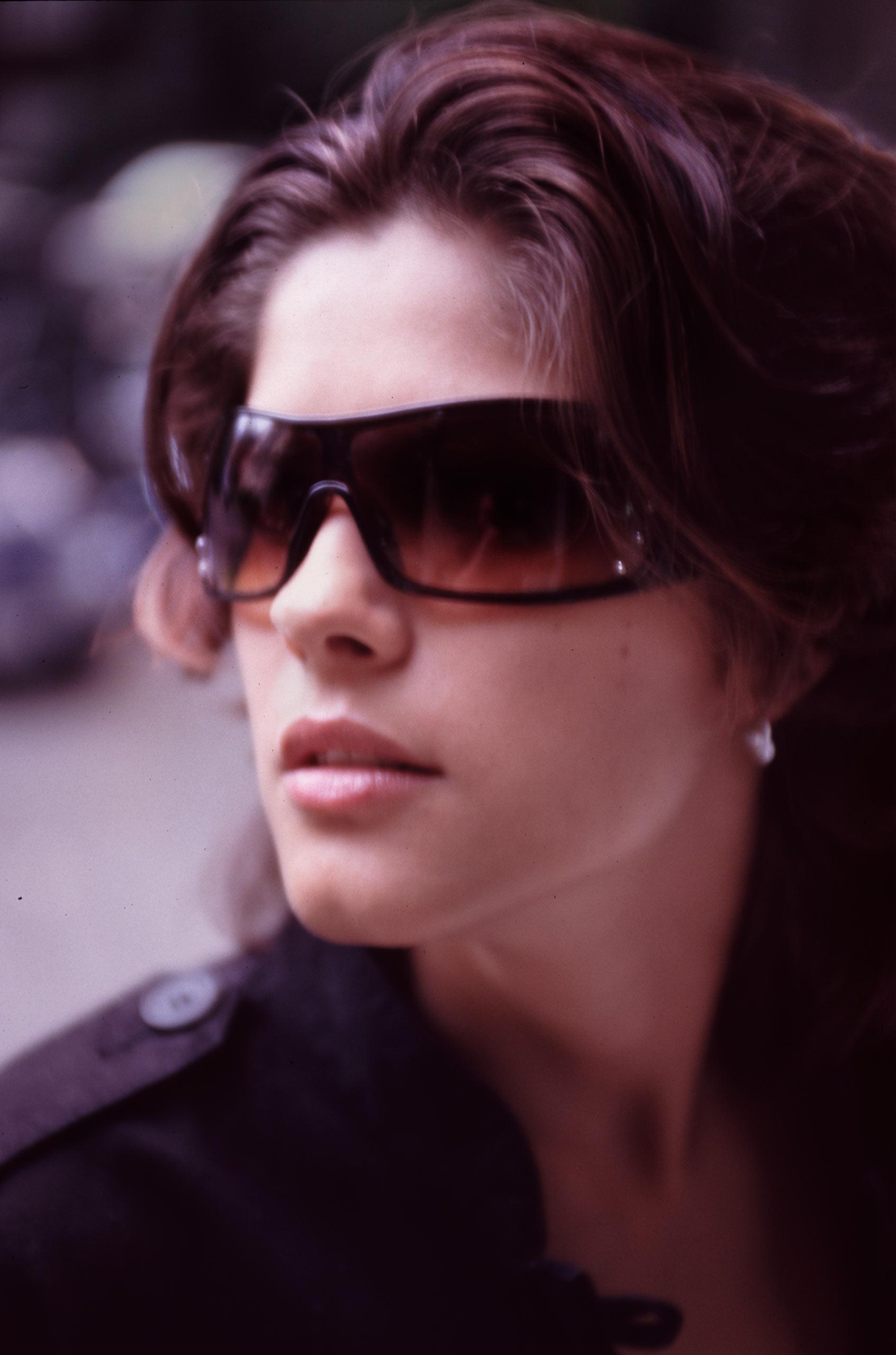 Das Foto zeigt ein stimmungsvolles Portrait einer jungen Frau mit Sonnenbrille
