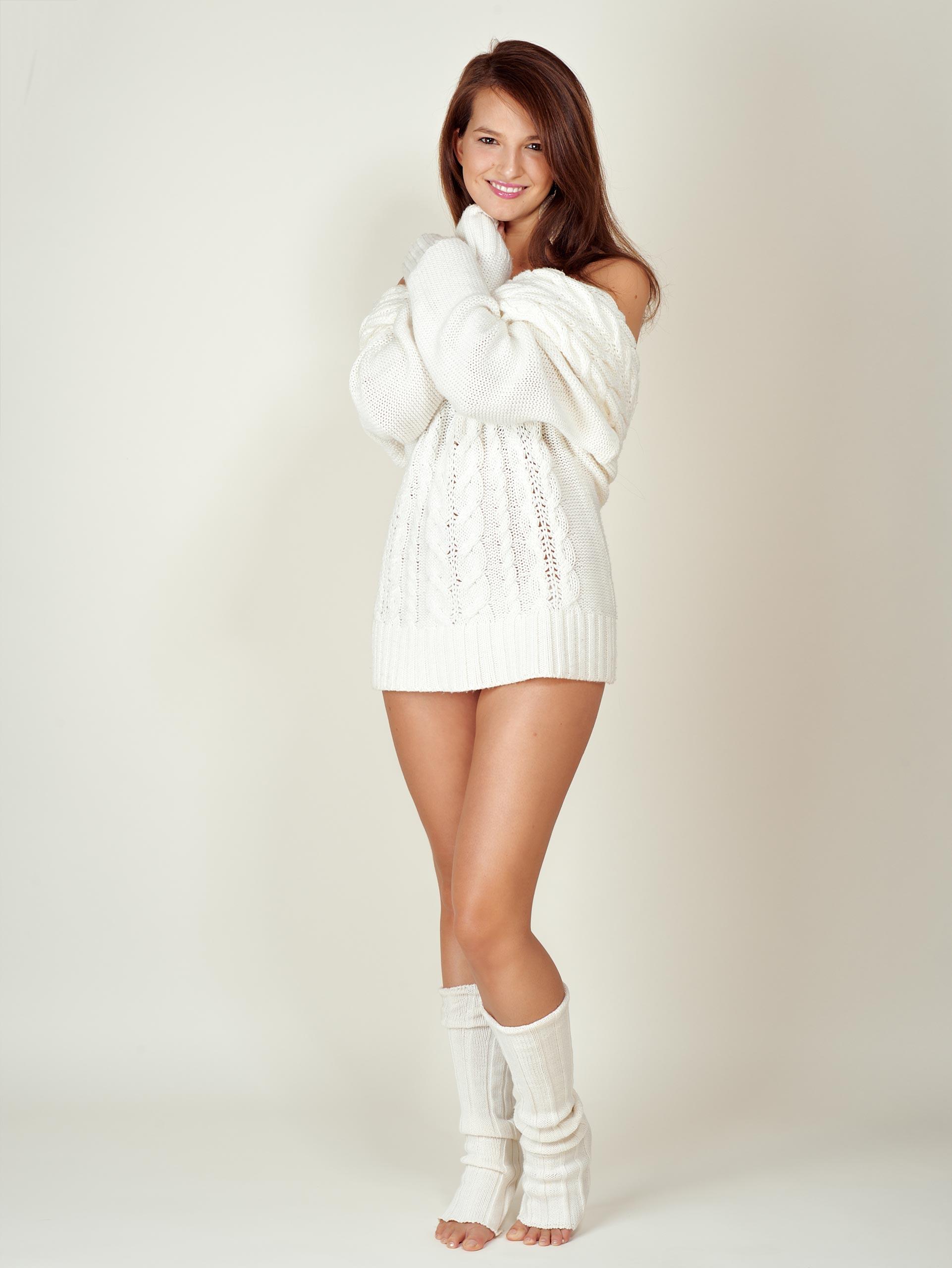 Das Foto zeigt eine junge Frau mit weißem Pullover und Stulpen